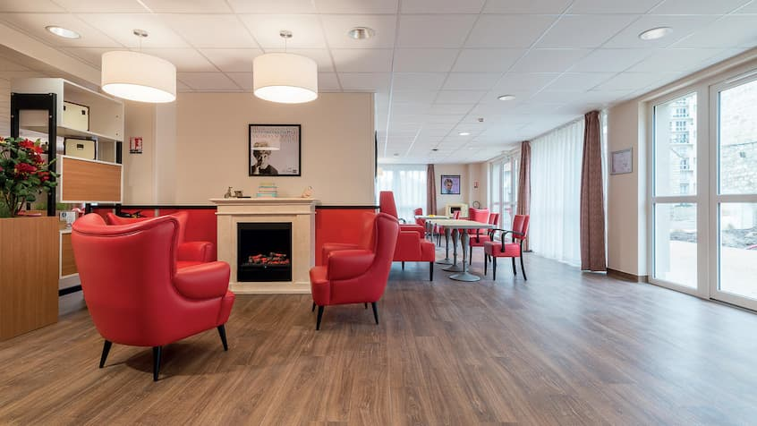 aged care flooring with red chair and tables