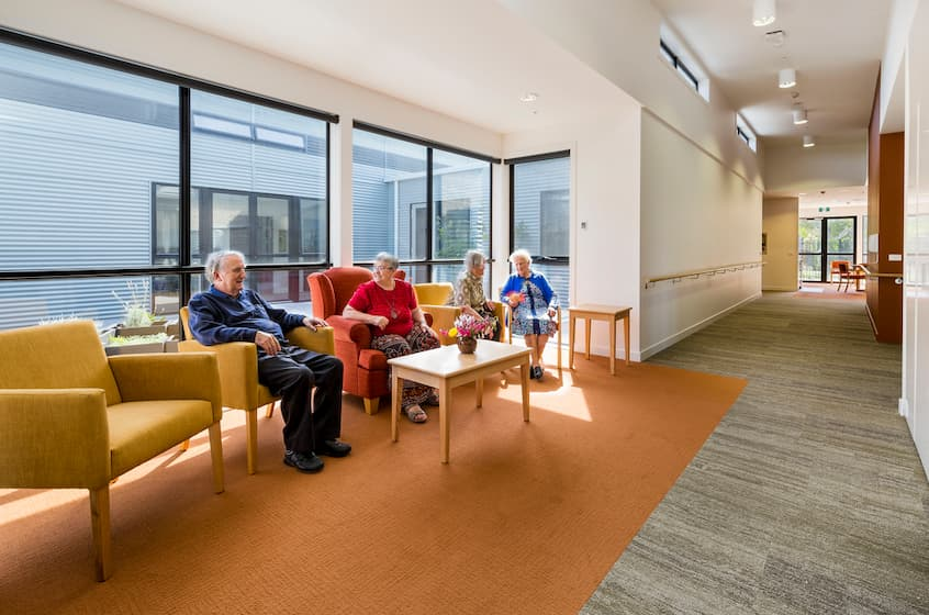 old people sitting in the aged care center on yellow chairs