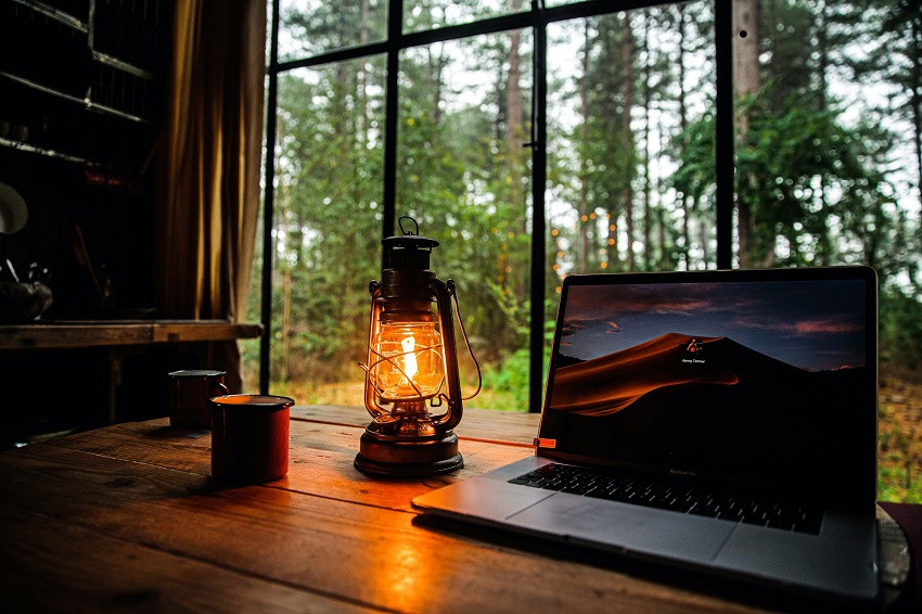 picture of lantern on a desk with a view of the woods